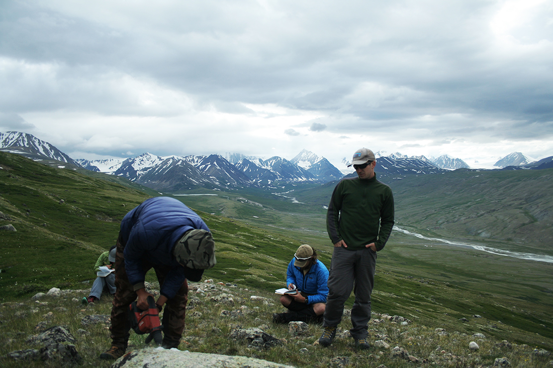 Oyungerel Sambuu, a student at the Mongolian University of Science and Technology, drills into a granite boulder for samples to trace the retreat of a glacier. The Potananin Glacier is visible in the distance. (Kevin Stark / Medill)