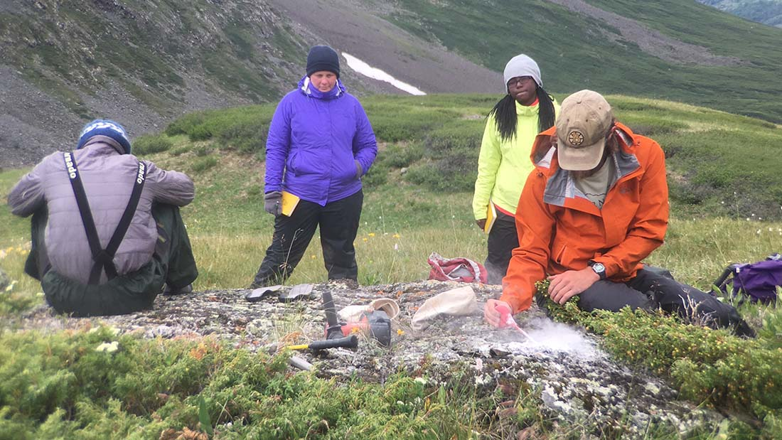 Gary Comer College Prep's Destiny Washington (yellow jacket) was chosen by her environmental science teacher Jessica Stevens (purple jacket) to participate in the Mongolian expedition. University of Maine's Nathan Norris cleans pulverized dust from a granite boulder after drilling holes to extract a sample. (Kevin Stark/Medill)