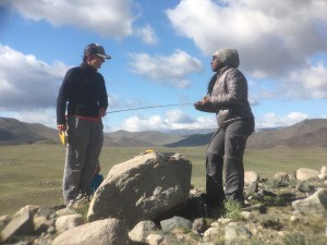 University of Maine's Mariah Radue and Gary Comer College Prep's Destiny Washington measure a granite boulder at the group's last field site. (Kevin Stark / Medill)