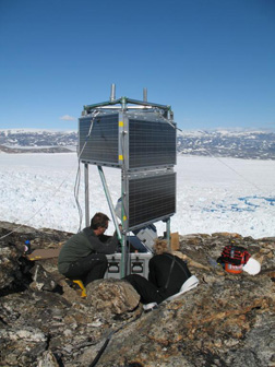 """Courtesy of M. Nettles   Installing a """"master"""" GPS station on a nunatak at Helheim Glacier. This station provides a fixed reference for GPS analysis, as well as collecting data via radio signal from stations on the glacier and transferring it to the research team via satellite telemetry."""