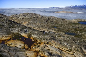 """Photo by Philip Walsh Greenland's vast ice sheet covers 90 percent of the island, but is drawing back its margins to as warmer temperatures melt the frozen layer.  Geologist George Denton and author Philip Conkling, who recently published """"The Fate of Greenland,"""" stand as specks on the barren bedrock."""