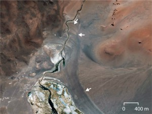 Satellite image of the northwest corner of Agua Caliente I. The white arrows indicate the location of the ancient abandoned shorelines, which form a bathtub-like ring pattern. Photograph courtesy of Christine Chen. (Neil Murthy/Medill)