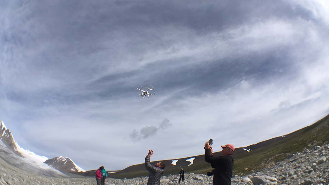 Lead scientist Aaron Putnam guides a drone in for a safe landing. The Comer Foundation's Scott Travis documents the event in a photo. The two were instrumental in troubleshooting the drone for scientific purposes. (Kevin Stark / Medill)